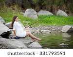 young beautiful pregnant woman fishing on the river bank - stock photo