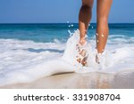 Woman Legs  Walking On The Beach