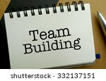 Team building memo written on a notebook with pen - stock photo