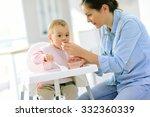 baby girl eating in her chair ... | Shutterstock . vector #332360339