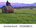 Man Sitting On A Bale Of Hay.