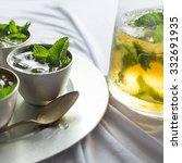 Small photo of A pitcher and pewter cups with mint julep.