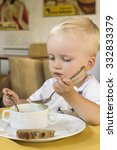 baby boy eating soup in a... | Shutterstock . vector #332833379