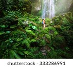 Small photo of A tired but happy tourist woman looking at the waterfall in the Central America jungles Ecotourism concept image travel