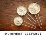Stock photo measuring metal scoops of whey protein powder against rustic grunge wood 333343631