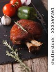Small photo of Baked pork shank and fresh vegetables close up on a slate board on the table. vertical