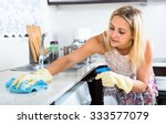 Small photo of Young housewife wearing rubber gloves is using cleaner in a spray bottle to clean kitchen