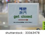 "Small photo of A multi-lingual sign in Korean, Chinese, Japanese, and English saying ""Get Closed"""
