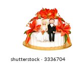 The happy couple ~ wedding cake adorned with a bride and groom, and vibrant orange lilies. - stock photo