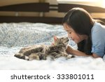 Stock photo beautiful asian girl lying with american shorthair cat on the bed 333801011