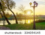 Stock photo landscape in park with trees and lamps near lake at sunset in autumn 334054145