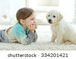Stock photo portrait of happy little girl at home with labrador puppy 334201421