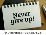 Never give up memo written on a notebook with pen - stock photo