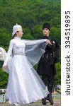 Small photo of Adygea, RUSSIA - JULY 25 2015: Young guy with a girl in Adyghe national costumes dancing traditional dance at an ethnofestival in the Foothills of Caucasus in Adygea