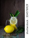Small photo of Lemons in in jar with lemon reamer on wooden background