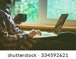 man lying with laptop drinking... | Shutterstock . vector #334592621