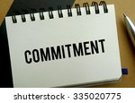 Commitment memo written on a notebook with pen - stock photo