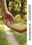 a the parent holds the hand of... | Shutterstock . vector #335294339