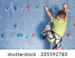 little boy climbing a rock wall ...