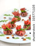 Small photo of Delicious air-dried beef ham - Italian Bresaola - stuffed with chopped rocked salad, roasted pine nuts, parmesan cheese and creamy balsamic vinegar, tied up with blanched chives