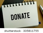 Donate memo written on a notebook with pen - stock photo