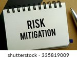 Risk mitigation memo written on a notebook with pen - stock photo