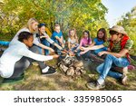 teens grilling sausages on... | Shutterstock . vector #335985065