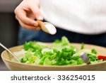 Young Woman Making Salad In Th...