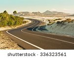 Curvy road through the dunes of Corralejo, Fuerteventura, in the Canary Islands, Spain. - stock photo
