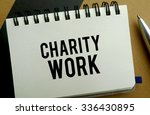 Charity work memo written on a notebook with pen - stock photo