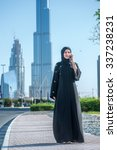 Small photo of Talking on the phone with a client in Dubai. Arab Business vumen hijab talking on a cell phone on the street on a background of skyscrapers of Dubai. The woman is dressed in a black abaya