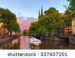 Stock photo beautiful sunset at the singel canal in amsterdam with the krijtberg church and a tourist boat 337607201
