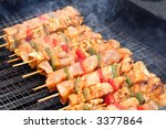 cooking white and red sausage on outdoor barbecue - stock photo