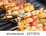 cooking chicken with pepper on outdoor barbecue - stock photo