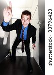 nice businessman standing in restroom with finger up pointing up - stock photo