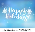 Brushlettering on a blue background with snowflakes Happy Holidays. Vector.