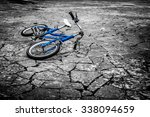 Small photo of Artistic dark vintage edit of a left children's bicycle on a cracked concrete floor, concept of interrupted childhood, abduction etc. Artistic selective color, blue on black and white background.