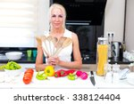 happy woman cooks in the kitchen   Shutterstock . vector #338124404