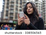 indian woman in city texting... | Shutterstock . vector #338506565