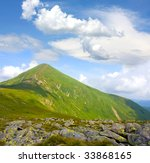 Green mountain under blue sky and clouds - stock photo