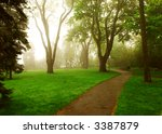 Path In A Green Foggy Park In...
