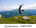 Jumping man in mountains - stock photo