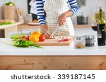 young woman cutting vegetables... | Shutterstock . vector #339187145