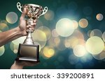 hand holding up a gold trophy... | Shutterstock . vector #339200891