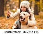Stock photo portrait of a beautiful young woman with her dog while walking in the autumn park 339215141