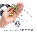 Small photo of Alternative health care fresh herbal and capsule in doctor 's hand on white background.