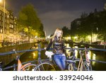 Small photo of Pretty young woman standing next to retro bicycle in Amsterdam