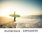 Surfer On The Beach Holding Is...