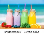 Stock photo assortment of fruit smoothies against a beach background 339555365