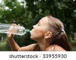 preteen girl drinking watter...   Shutterstock . vector #33955930